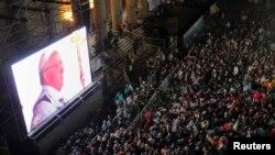 Fidèl katolik ap swiv seremini envestiti Pap François sou yon ekran jeyan tou pre Katedral Metwopolitèn Buenos Aires la (madi 19 mas 2013).