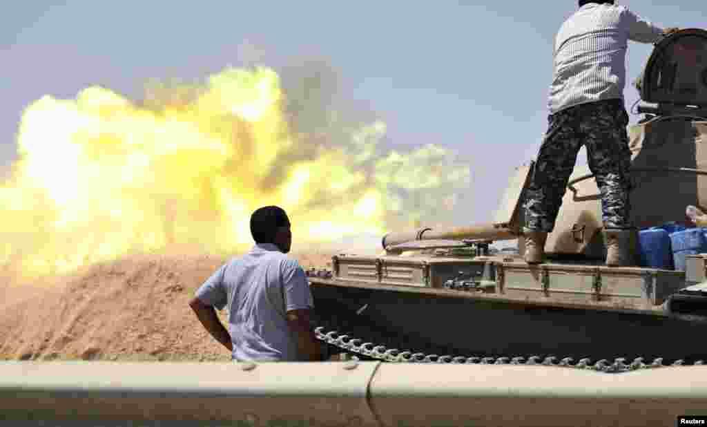 Liviya Mudofaa kuchlariga qarashli tank muxolif jangari guruhlar bilan bo'lib o'tgan to'qnashuvda o't ochmoqda, Tripoli, Liviya, 22-avgust, 2014-yil.