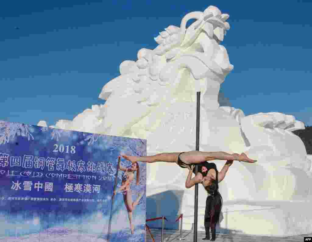 2018年12月20日,在中国黑龙江省东北部漠河的零下23摄氏度的严寒下,在龙形雪雕前面举行钢管舞比赛,一位舞者参赛。漠河在中国领土的最北端。
