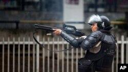 Un policía dispara con perdigones a manifestantes durante una protesta en Caracas.