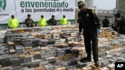 FILE - Colombia National Police Chief Rodolfo Palomino walks on seized packages of cocaine displayed for a press briefing in Cartagena, April 10, 2014. U.S. and Colombian authorities have issued warrants for 29 suspects accused of smuggling cocaine.