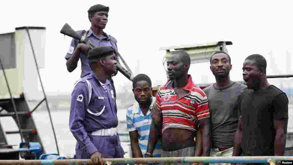 Suspected pirates are paraded aboard a naval ship after their arrest by the Nigerian Navy at a defence jetty in Lagos, August 20, 2013.