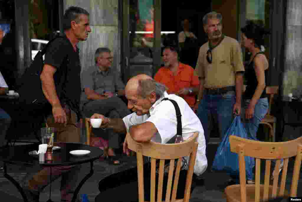 People sit outside a coffee shop in central Athens, July 20, 2015.