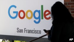 In this May 1, 2019, file photo, a person walks past a Google sign in San Francisco. (AP Photo/Jeff Chiu, File)