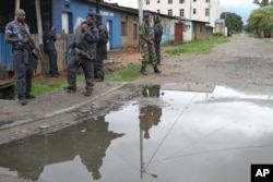 FILE - Burundian police and soldiers guard a deserted street in Bujumbura, Burundi, Nov. 8, 2015. Rising violence in Burundi is sparking calls for greater international attention.