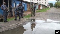 FILE - Burundian police and soldiers guard a deserted street in Bujumbura, Burundi.