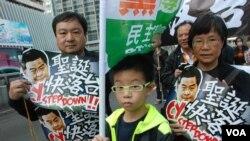香港市民蔡先生與太太帶同10歲兒子參加遊行,表達對特首梁振英的不滿(美國之音湯惠芸拍攝)