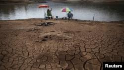 Những người câu cá ngồi gần một khu đất nứt nẽ vì đập Atibainha cạn kiệt do hạn hán kéo dài ở Nazare Paulista, trong bang Sao Paulo, 17/10/2014