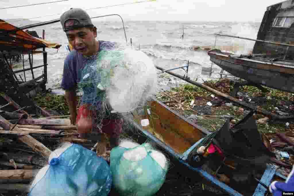 11月8日,在馬尼拉以南的一個城鎮,一名漁夫在安全返回陸地時拖著自己的網。