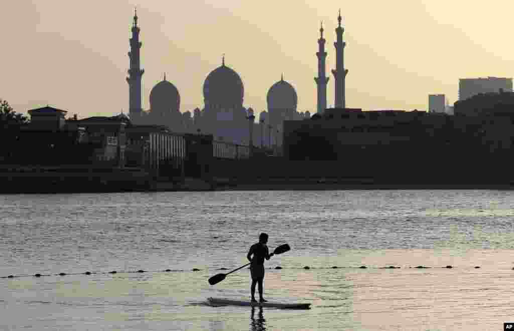 អ្នកជិះទូកម្នាក់ចែវទូកនៅពីមុខព្រះវិហារ Sheikh Zayed Grand Mosque នៅក្នុងក្រុង Abu Dhabi ប្រទេសអេមីរ៉ាតអារ៉ាប់រួម។