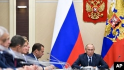 FILE - Russian President Vladimir Putin, right, presides over a cabinet meeting at the Novo-Ogaryovo residence outside Moscow, Russia.