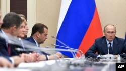 Russian President Vladimir Putin, right, presides over a cabinet meeting at the Novo-Ogaryovo residence outside Moscow, Russia, Sept. 27, 2017. Russian officials reported the destruction of the country's last remaining artillery projectiles filled with a toxic agent to Putin Wednesday.