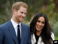 FILE - Britain's Prince Harry and his fiancee, Meghan Markle, pose for photographers in the grounds of Kensington Palace in London, Nov. 27, 2017.