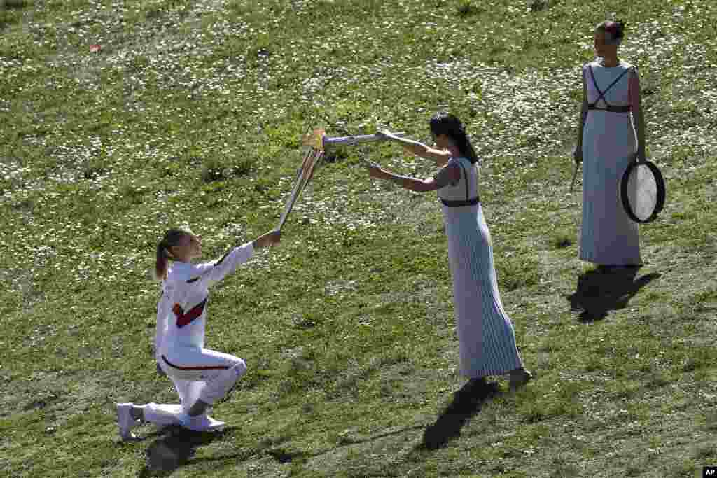 Greek actress Xanthi Georgiou, center, playing the role of the High Priestess, lights the torch of the 2020 Tokyo Olympic Games, held by Greek shooting Olympic champion Anna Korakaki, left,  during the flame lighting ceremony at the closed Ancient Olympia site in southern Greece.