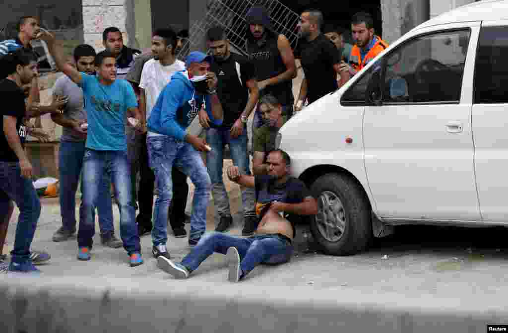 Palestinians try to evacuate a wounded man during clashes with Israeli troops at Qalandia checkpoint near the occupied West Bank city of Ramallah, Oct. 6, 2015.