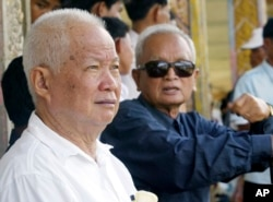 FILE - Former Khmer Rouge leaders Khieu Samphan, left, and Nuon Chea sit together during funeral services for Khieu Ponnary, the first wife of Khmer Rouge leader Pol Pot, in the former Khmer Rouge stronghold of Pailin, northwestern Cambodia, July 3, 2003.
