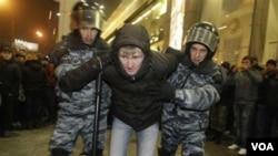 2 polisi di Moskow menangkap seorang nasionalis muda dalam suatu unjuk rasa di Moscow.