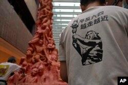 """Para aktivis di kampus Universitas Hong Kong, membersihkan sisa-sisa dekorasi """"Pilar Kesedihan Nasional"""" untuk memperingati korban Tiananmen. (AP)."""