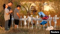 Miranda Hernandez (L) prays at sunset with father Kenneth and mother Irene at a row of crosses near the site of the shooting at the First Baptist Church of Sutherland, Texas, Nov. 6, 2017.
