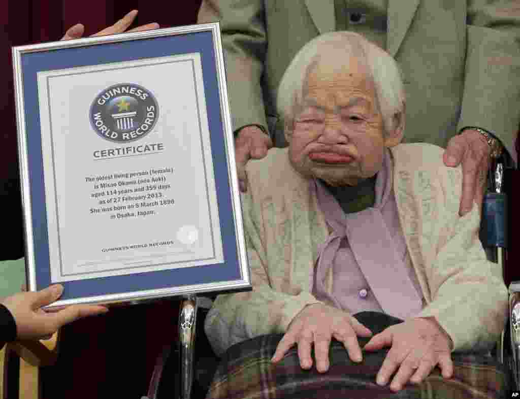 Japan's 114-year-old Misao Okawa receives a certificate of the world's oldest woman, which was presented to her by Guinness World Records Japan Country Manager Erika Ogawa, at a nursing home in Osaka, western Japan.
