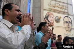 FILE - Journalists and activists protest against the restriction of press freedom and to demand the release of detained journalists, in front of the Press Syndicate in Cairo, April 26, 2016.