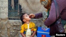 A boy receives polio vaccine drops, during an anti-polio campaign, in a low-income neighborhood in Karachi, Pakistan, April 9, 2018.