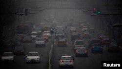 Xe cộ chạy trên đường phố ở Bắc Kinh bị bao phủ bởi làn khói sương dày đặc.