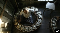 Mao Phoeung, a Cambodian music master, plays traditional circular gongs at his home in Phnom Penh, file photo. Mao Phoeung's teachings are funded by the Cambodian Living Arts program, part of an effort by the Cambodian-American group to breath new life in