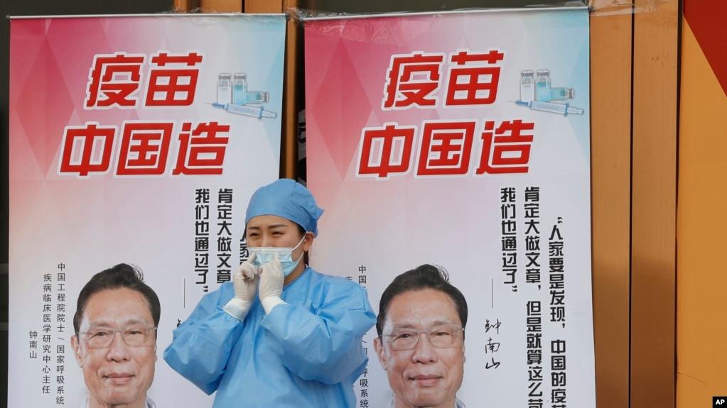 """北京一位医护人员站在""""疫苗中国造""""宣传画前。(2021年4月9日)(photo:VOA)"""