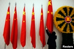 FILE - An official adjusts Chinese flags before Chinese Premier Wen Jiabao arrives for the 21st ASEAN (Association of Southeast Asian Nations) and East Asia summits in Phnom Penh November 18, 2012.