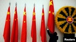 រូបឯកសារ៖ មន្ត្រីម្នាក់រៀបចំទង់ជាតិចិន មុនពេលលោកនាយករដ្ឋមន្ត្រីចិន Wen Jiabao មកចូលរួមកិច្ចប្រជុំកំពូលអាស៊ាន និងអាស៊ីខាងកើត នៅរាជធានីភ្នំពេញកាលពីខែវិច្ឆិកា ឆ្នំា២០១២។ (REUTERS/Damir Sagolj)