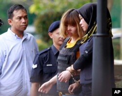 Vietnamese suspect Doan Thi Huong (second from right) is escorted by police officers from court in Sepang, Malaysia, March 1, 2017. Two young women accused of smearing VX nerve agent on Kim Jong Nam, the estranged half brother of North Korea's leader, were charged with murder.