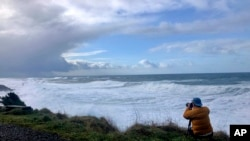 Seorang pria mengabadikan gelombang pasang ekstrem di Rodea Point, di Lincoln County, Oregon, 11 Januari 2020. (Foto: AP)