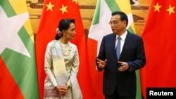 18일 중국을 방문한 미얀마의 아웅산수치 국가자문역 겸 외무장관(왼쪽)이 리커창 중국 총리와 양국간 협정 조인식에서 대화하고 있다.