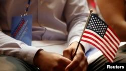 一名新公民在紐約公共圖書館的公民宣誓儀式上手持美國國旗(2018年7月3日)