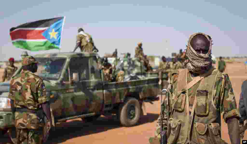 A South Sudanese government soldier stands with others near their vehicles, after government forces retook Bentiu, capital of Unity State, from opposition fighters on Jan. 10.