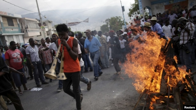 A protester playing two vuvuzelas walks next to a fire lighted for a ceremony during a demonstration against the government in Port-au-Prince, Haiti, Jan. 25, 2016.
