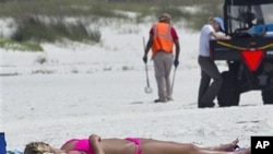 Madison Smith of Cincinnati lies in the sun on the beach in Perdido Key, Fla., as oil spill cleanup workers search for tar balls a year after the Deepwater Horizon disaster, April 19 2011