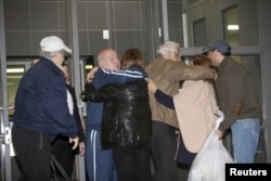Family and friends embrace Bahram Mechanic (in the blue jump suit) and Khosrow Afghahi (in the tan jacket) at Federal Detention Center Houston, Texas, Jan.17, 2016. Several Iranian-Americans held in U.S. prisons after being charged or convicted for sanctions violations have been released under a prisoner swap.