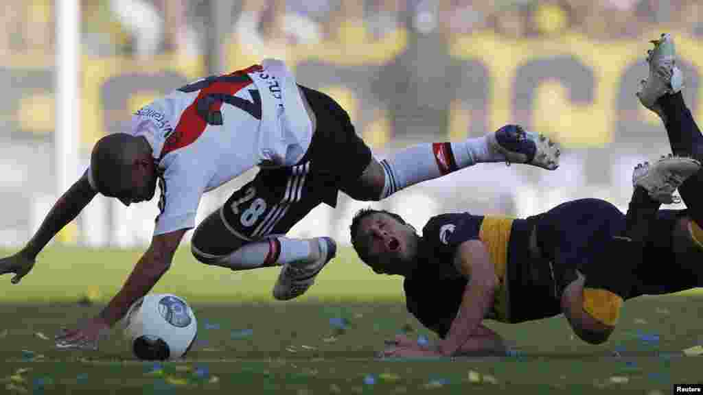 Cristian Ledesma (kushoto) mchezaji wa timu ya River Plate agon'gana na Pablo Ledesma wa Boca Junior walipokuwa wanakimbilia mpira katika mechi ya ligi ya kwanza ya Argentine mjini Buenos Aires Mei 5, 2013.
