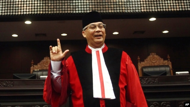 FILE -  Indonesia's top judge Akil Mochtar poses for photos during a swearing-in ceremony in Jakarta. Mochtar on Indonesia's Constitutional Court has been arrested on suspicion of bribery in the country's laest high-profile graft scandal.