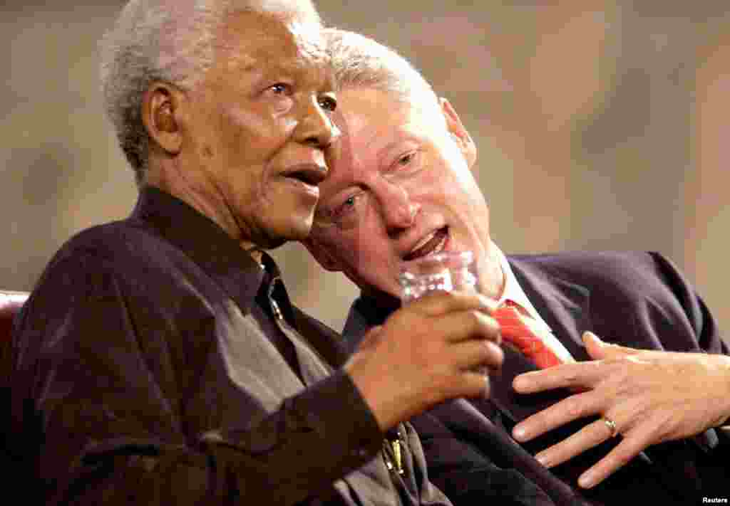 Former U.S President Bill Clinton and former South African President Nelson Mandela speak during a Gala night in Westminster Hall, London, July 2, 2003.