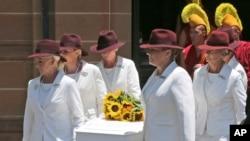 12月23日澳大利亚悉尼举行的葬礼上,身穿白衣的葬仪人员扶抬着咖啡馆经理托尼约翰逊的棺木。