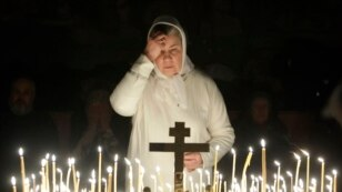 FILE - A believer prays in a church in Moscow, Russia, Jan. 6, 2010.