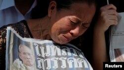 2016年10月14日,在泰国国王普密蓬遗体从他去世的医院移送到曼谷大皇宫的路上,一个女子在路边哭泣。