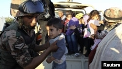 A Jordanian soldier helps Syrian refugees fleeing violence in their country after they crossed the border into Jordanian territory with their families from Syria into Jordan, near the town of Ramtha September 15, 2012. REUTERS/Muhammad Hamed (JORDAN - Tag