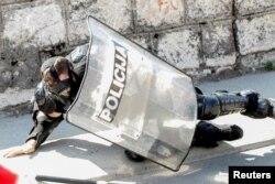 Pripadnik crnogorske policije pritiže se sa zemlje nakon guranja sa demonstrantima koji se protive ustoličenju mitropolita SPC Joanikija u Cetinju, 4 septembra 2021. (Foto: Rojters, Stevo Vasiljević)