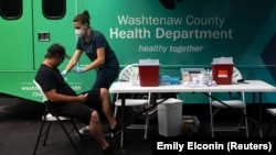 Nurse Elizabeth Head gets ready to give Andrew Seay his COVID-19 vaccine at Grace Fellowship Church in Ypsilanti, Michigan, U.S., August 7, 2021. (REUTERS/Emily Elconin)