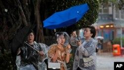 Para pejalan kaki berusahan menahan payung mereka di tengah terpaan angin kencang yang diakibatkan badai tropis Pakhar dekat Victoria Habour di Hong Kong, 27 Agustus 2017.