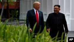 President Donald Trump walks with North Korean leader Kim Jong Un on Sentosa Island, Tuesday, June 12, 2018, in Singapore.